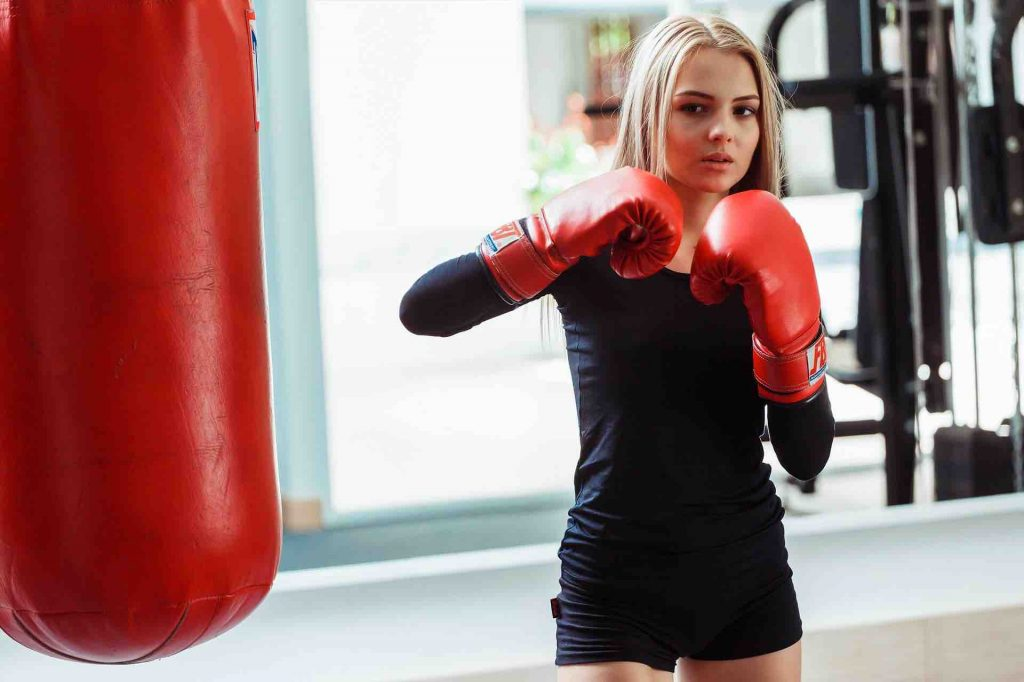 Woman boxing with an apartment punching bag