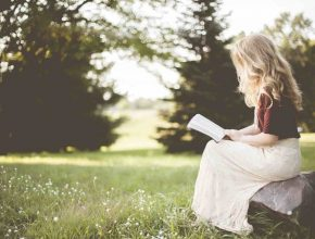 Picture of a healthy woman reading outside