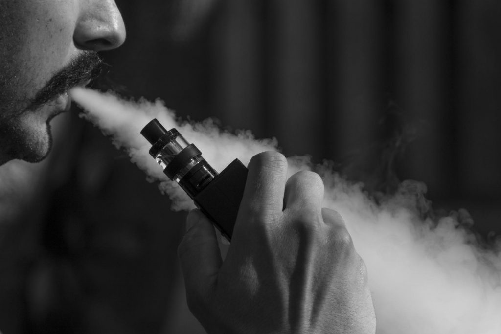 Black and white photo of a man vaping
