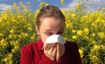 Woman blowing her nose in a field of flowers