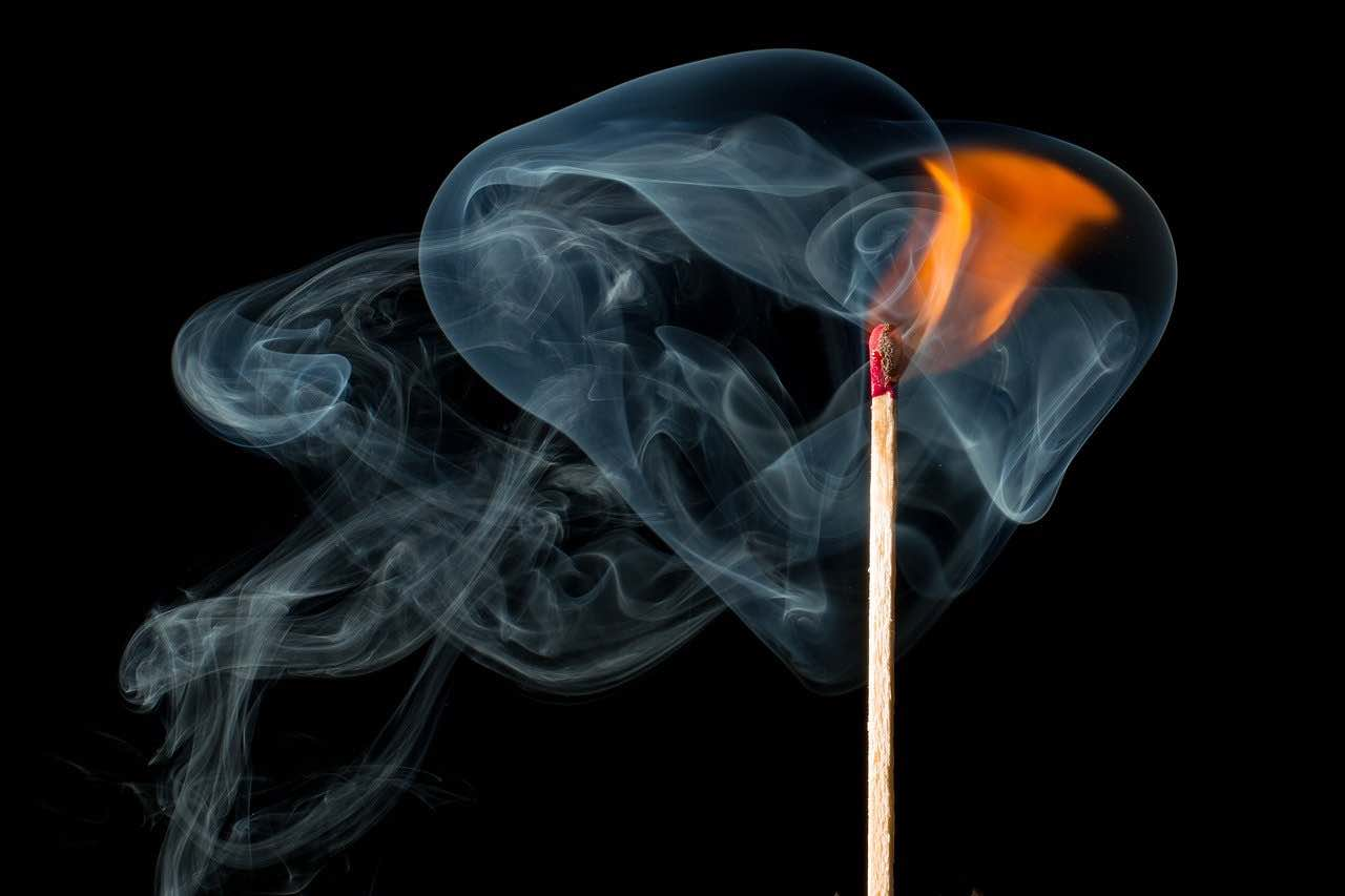 Picture of a lit match giving off smoke