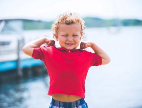 Healthy little boy flexing muscles
