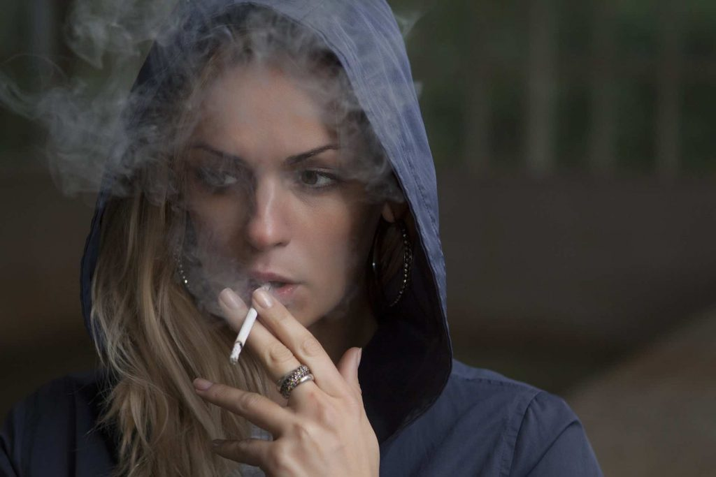 Woman smoking a cigarette with her hood up